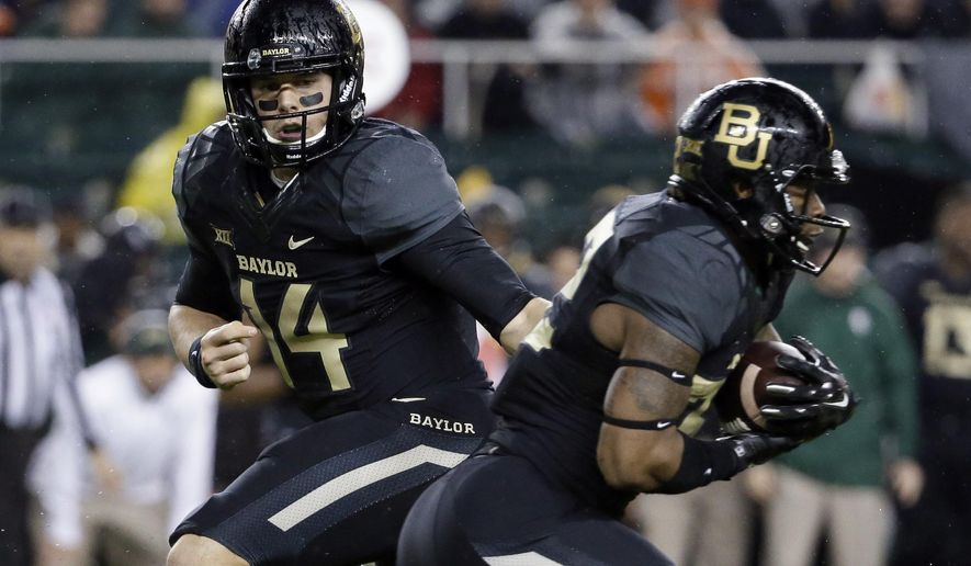 Baylor quarterback Bryce Petty (14) hands the ball off to running back Shock Linwood, right, in the first half of an NCAA college football game against Oklahoma State, Saturday, Nov. 22, 2014, in Waco, Texas. (AP Photo/Tony Gutierrez)