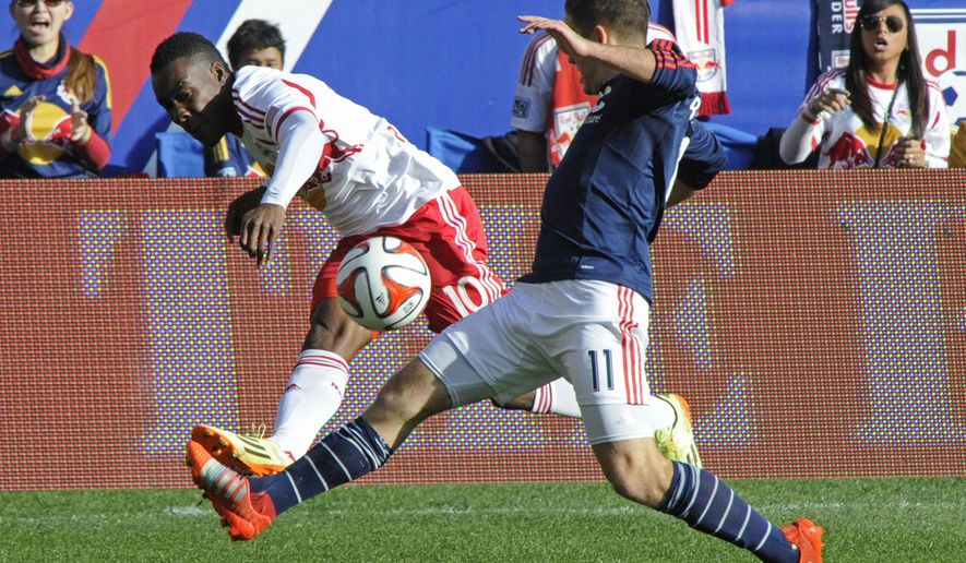 New England Revolution forward Kelyn Rowe, right, blocks a shot by New York Red Bulls midfielder Lloyd Sam during the first half of an MLS Eastern Conference finals soccer match Sunday, Nov. 23, 2014, in Harrison, N.J.. (AP Photo/Bill Kostroun)