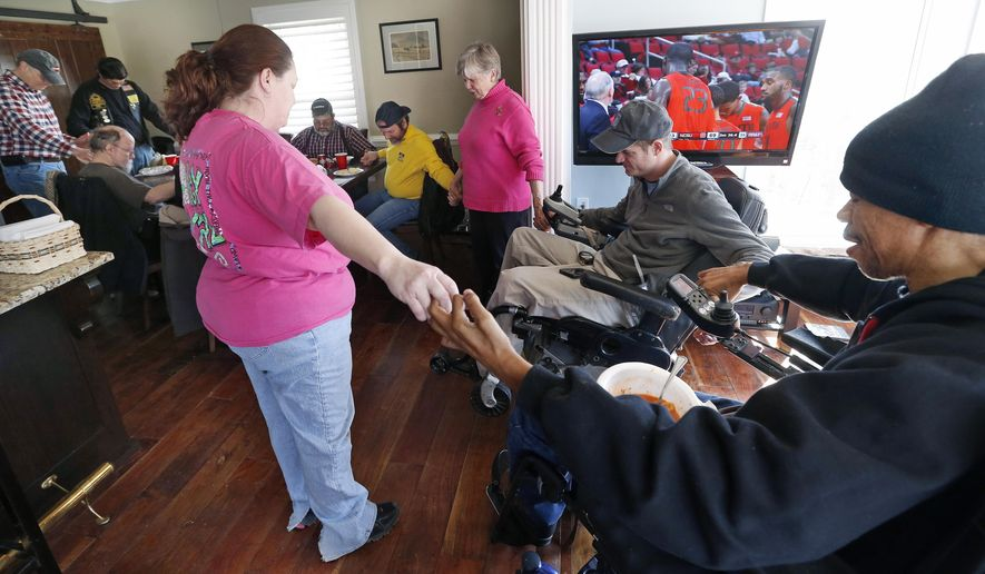 ADVANCE FOR MONDAY NOV. 24 AND THEREAFTER - Members of the Hogs and Heroes Foundation and friends pray with Nancy Howard, center, and her son James Howard , second from right, Saturday, March 1, 2014. The foundation was building a ramp for wheelchairs at James Howard's Chesterfield, Va. home which he was turning into a resort for veterans. (AP Photo/Richmond Times-Dispatch, Alexa Welch Edlund)  (AP Photo/Richmond Times-Dispatch, Alexa Welch Edlund) (AP Photo/Richmond Times-Dispatch, Alexa Welch Edlund)