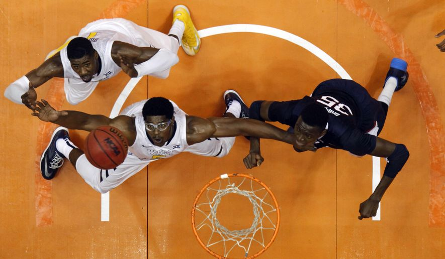 West Virginia forward Devin Williams, center, and teammate forward Jonathan Holton, left, battle for a rebound against UConn center Amida Brimah during a NCAA college basketball game in San Juan, Puerto Rico, Sunday, Nov. 23, 2014. (AP Photo/Ricardo Arduengo)