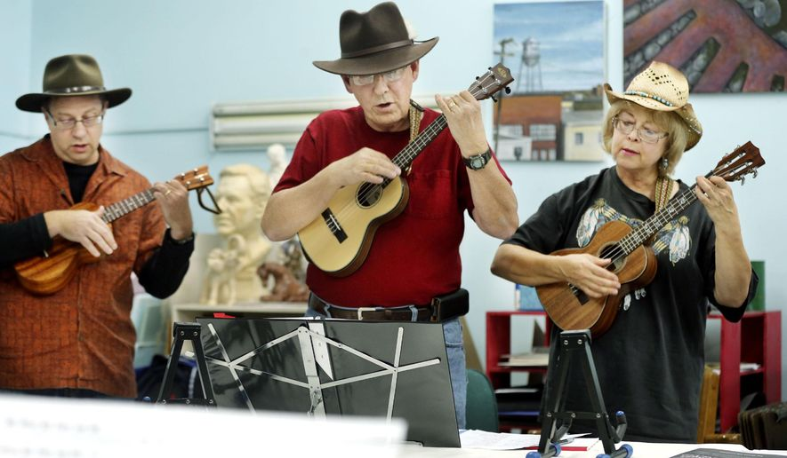 ADVANCE FOR MONDAY NOV. 24 - In this Nov. 4, 2014 photo, David Bartell, left, Larry Burke, center, and Linda Burke play ukuleles during a meeting of their ukulele club in Berryville, Va. (AP Photo/The Winchester Star, Scott Mason)