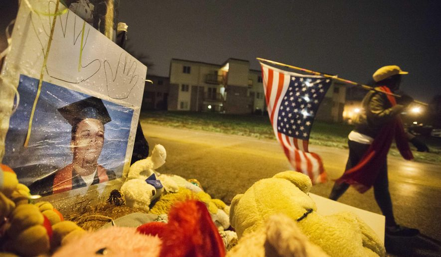 A high school graduation photo of Michael Brown stands at a memorial more than three months after the black teen was shot and killed nearby by a white policeman as Gina Gowdy, of Ferguson, Mo., walks past carrying an American flag, Saturday, Nov. 22, 2014, in Ferguson, Mo. Ferguson and the St. Louis region are on edge in anticipation of the announcement by a grand jury whether to criminally charge Officer Darren Wilson in the killing of 18-year-old Michael Brown. (AP Photo/David Goldman)
