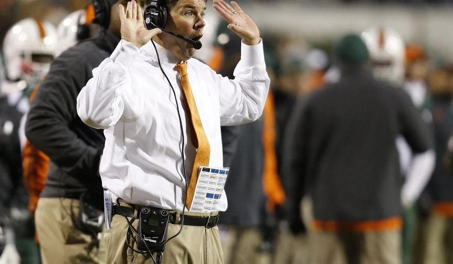 Miami head coach Al Golden directs his team during the second half of an NCAA college football game against Virginia in Charlottesville, Va., Saturday, Nov. 22, 2014. Virginia won the game 30-13. (AP Photo/Steve Helber)
