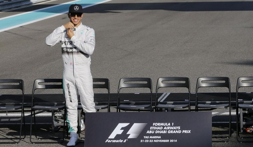 Mercedes driver Lewis Hamilton of Britain arrives for the Formula one drivers end session group photo ahead of the Abu Dhabi Formula One Grand Prix at the Yas Marina racetrack in Abu Dhabi, United Arab Emirates, Sunday, Nov. 23, 2014. (AP Photo/Hassan Ammar)