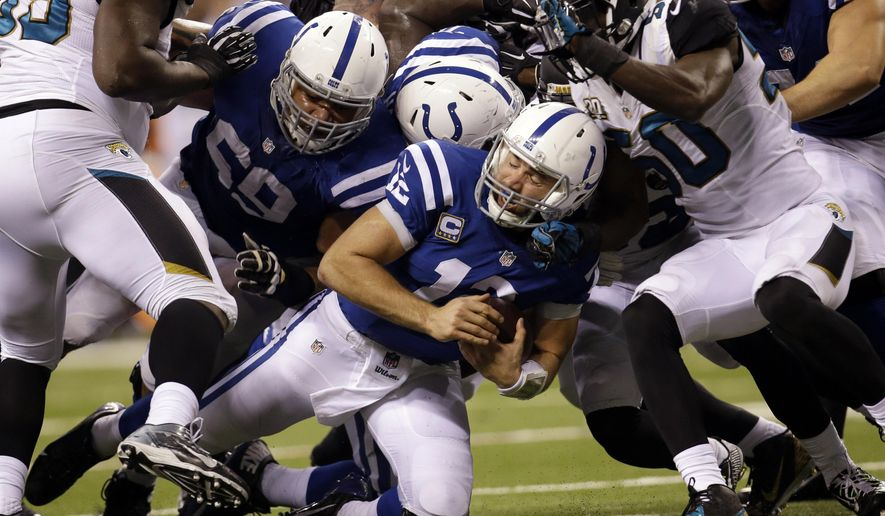 Indianapolis Colts quarterback Andrew Luck (12) is tacked by Jacksonville Jaguars outside linebacker Telvin Smith (50) during the second half of an NFL football game Sunday, Nov. 23, 2014, in Indianapolis. (AP Photo/AJ Mast)