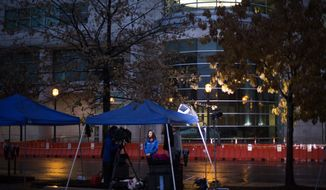 A television news reporter conducts a broadcast outside the Buzz Westfall Justice Center where a grand jury is expected to convene Monday to consider possible charges against the police officer who fatally shot Michael Brown in nearby Ferguson, Sunday, Nov. 23, 2014, in Clayton, Mo. Ferguson and the St. Louis region are on edge in anticipation of the announcement by a grand jury whether to criminally charge officer Darren Wilson in the killing of 18-year-old Michael Brown. (AP Photo/David Goldman) **FILE**