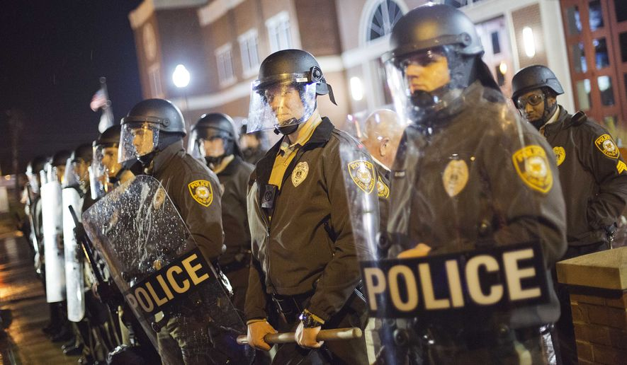 Police stand guard during a demonstration outside the Ferguson Police Department, Sunday, Nov. 23, 2014, in Ferguson, Mo. Ferguson and the St. Louis region are on edge in anticipation of the announcement by a grand jury whether to criminally charge Officer Darren Wilson in the killing of 18-year-old Michael Brown. (AP Photo/David Goldman)