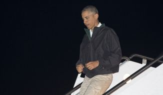 President Barack Obama deplanes from Air Force One, Sunday, Nov. 23, 2014, in Andrews Air Force Base, Md., as he returns form Las Vegas. (AP Photo/Carolyn Kaster)