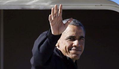 President Barack Obama waves as he boards Air Force One at McCarran International Airport, Sunday, Nov. 23, 2014, in Las Vegas. (AP Photo/Isaac Brekken)