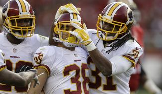Washington Redskins cornerback Greg Ducre (38) celebrates after intercepting a pass with cornerback Bashaud Breeland, left, and strong safety Brandon Meriweather (31) against the San Francisco 49ers during the third quarter of an NFL football game in Santa Clara, Calif., Sunday, Nov. 23, 2014. (AP Photo/Ben Margot)