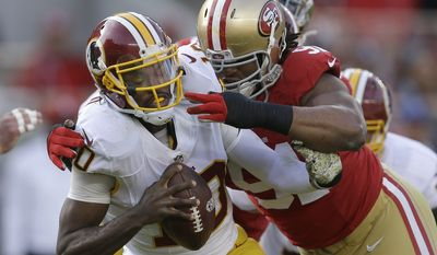 Washington Redskins quarterback Robert Griffin III, left, is sacked by San Francisco 49ers defensive tackle Ray McDonald during the first quarter of an NFL football game in Santa Clara, Calif., Sunday, Nov. 23, 2014. (AP Photo/Ben Margot)