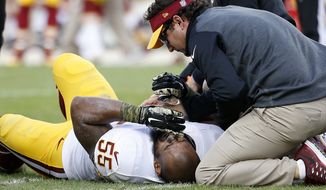 Washington Redskins outside linebacker Adam Hayward (55) is tended to by trainers after being injured during the third quarter of an NFL football game against the San Francisco 49ers in Santa Clara, Calif., Sunday, Nov. 23, 2014. (AP Photo/Tony Avelar)