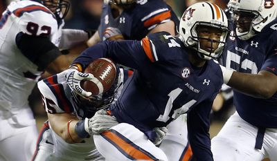Auburn quarterback Nick Marshall (14) scrambles for yardage during the first half of an NCAA college football game against Samford on Saturday, Nov. 22, 2014, in Auburn, Ala. (AP Photo/Butch Dill)