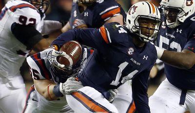 Auburn quarterback Nick Marshall (14) scrambles for yardage during the first half of an NCAA college football game against Samford on Saturday, Nov. 22, 2014, in Auburn, Ala. (AP Photo/Butch Dill)