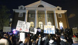 Protestors carry signs and chant slogans in front of the Phi Kappa Psi fraternity house at the University of Virginia late Saturday night, Nov. 22, 2014, in Charlottesville, Va. The protest, the most well-attended of several throughout the day, was in response to the university's reaction to an alleged sexual assault of a student revealed in a recent Rolling Stone article. (AP Photo/The Daily Progress, Ryan M. Kelly)