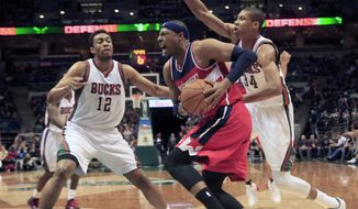 Washington Wizards forward Paul Pierce, center, drives to the basket against the defense of Milwaukee Bucks forward Jabari Parker, left, and guard Giannis Antetokounmpo, right, during the first half of an NBA basketball game Saturday, Nov. 22, 2014, in Milwaukee. (AP Photo/Darren Hauck)