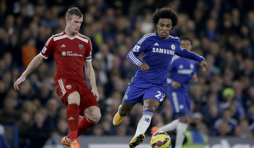 Chelsea's Willian, right, competes for the ball with West Bromwich Albion's Chris Brunt during the English Premier League soccer match between Chelsea and West Bromwich Albion at Stamford Bridge stadium in London, Saturday, Nov. 22, 2014.  (AP Photo/Matt Dunham)