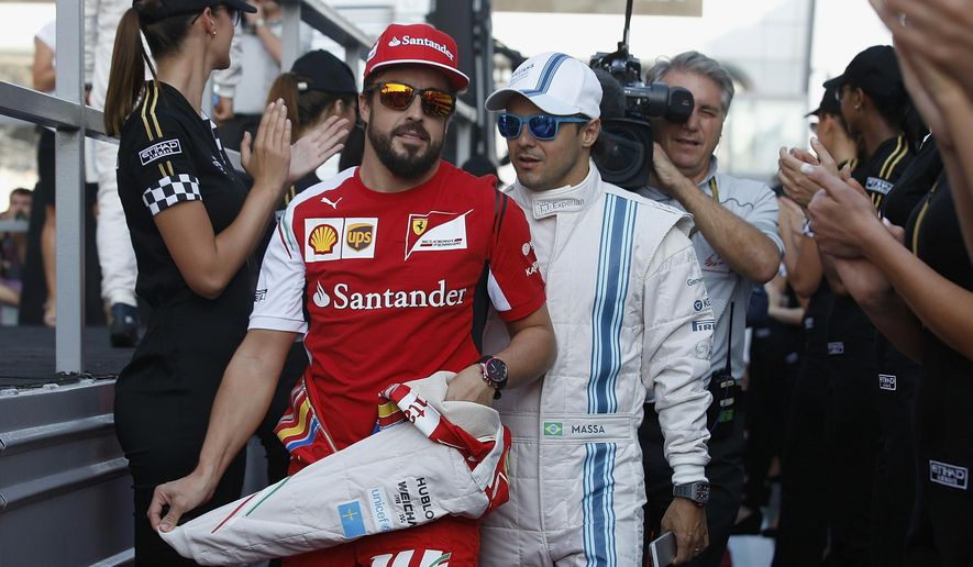 Ferrari driver Fernando Alonso of Spain, left and Williams driver Felipe Massa of Brazil arrive for the drivers parade for the Emirates Formula One Grand Prix at the Yas Marina racetrack in Abu Dhabi, United Arab Emirates, Sunday, Nov. 23, 2014. (AP Photo/Luca Bruno)