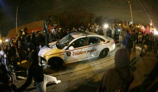 A protester squirts lighter fluid on a police car as the car windows are shuttered near the Ferguson Police Department after the announcement of the grand jury decision not to indict police officer Darren Wilson in the fatal shooting of Michael Brown, an unarmed black 18-year-old, Monday, Nov. 24, 2014, in Ferguson, Mo (AP Photo/Charlie Riedel)