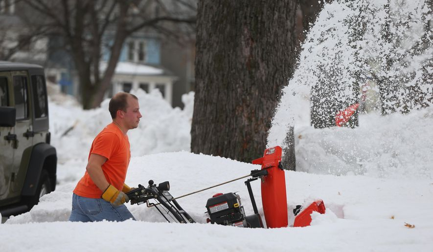 With temperatures in the high 40's John Fritz clears his neighbors driveway in a tee shirt on Oakhurst in South Buffalo Sunday, Nov. 23, 2014. (AP Photo/The Buffalo News, Mark Mulville)