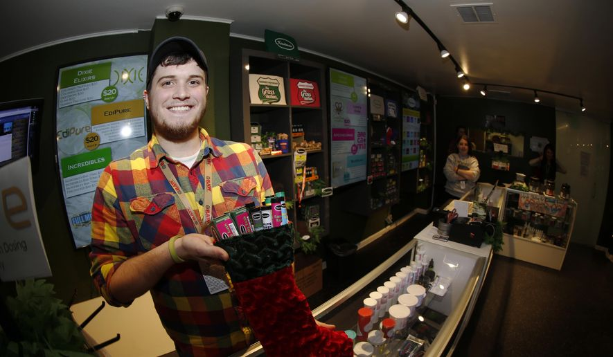 In this photograph taken on Thursday, Nov. 20, 2014, bud tender Maxwell Bradford shows off holiday stocking filled with more than $500 of marijuana and accessories for sale for the holiday season in a recreational marijuana shop in northwest Denver. (AP Photo/David Zalubowski)