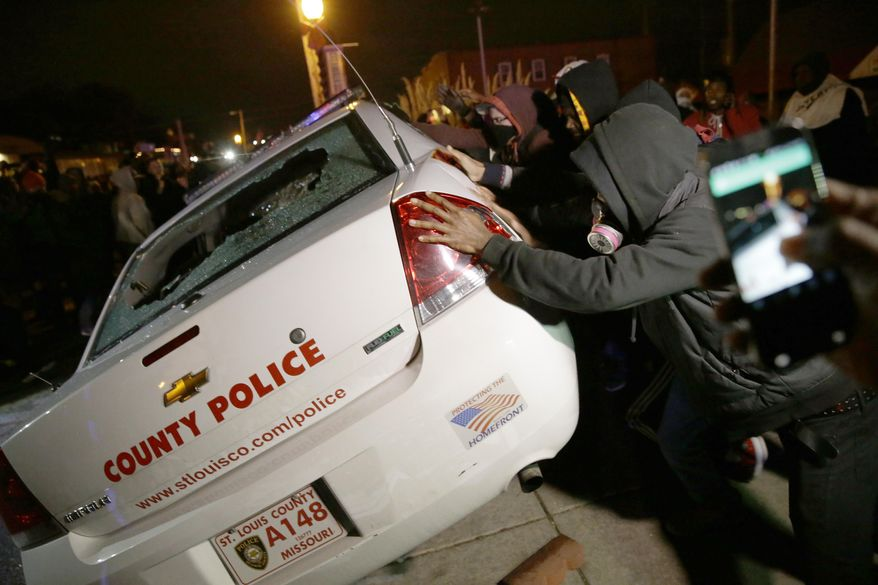 A group of protesters vandalize a police vehicle after the announcement of the grand jury decision not to indict police officer Darren Wilson in the fatal shooting of Michael Brown, an unarmed black 18-year-old, Monday, Nov. 24, 2014, in Ferguson, Mo. (AP Photo/David Goldman)