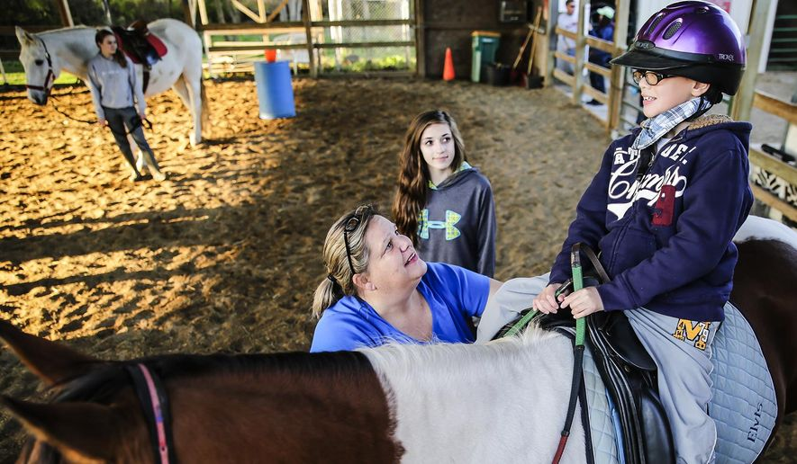 In this Oct. 22, 2014 photo, Lisa Afshari talks with Ethan Sobolevsky, 10, of Plainfield, Ill., during a therapeutic riding session at Ready Set Ride in Plainfield. Sobolevsky has been receiving therapeutic riding since he was 3 years old. (AP Photo/The Herald-News, Lathan Goumas)  MANDATORY CREDIT