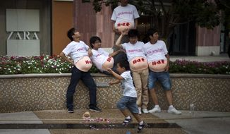 Men wearing fake pregnant bellies rest near a fountain after posing for advertisement photos for a baby product brand while a boy runs past outside a shopping mall in Beijing on Aug. 13, 2011. (Associated Press) **FILE**