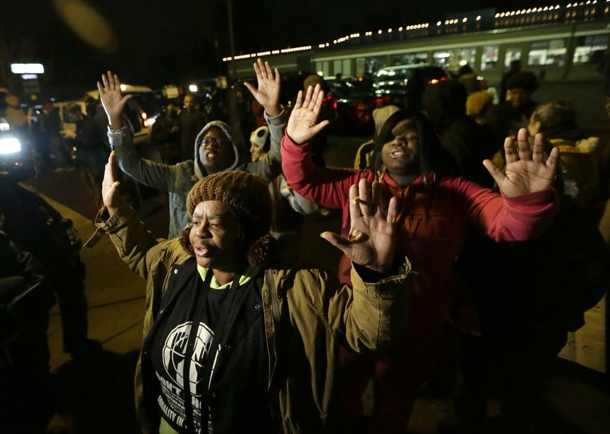 Barbara Jones, joined by other protesters, raises her hands, Monday, Nov. 24, 2014, in Ferguson, Mo., more than three months after an unarmed black 18-year-old man was shot and killed there by a white policeman. Ferguson and the St. Louis region are on edge in anticipation of the announcement by a grand jury whether to criminally charge Officer Darren Wilson in the killing of Michael Brown. (AP Photo/Charlie Riedel)
