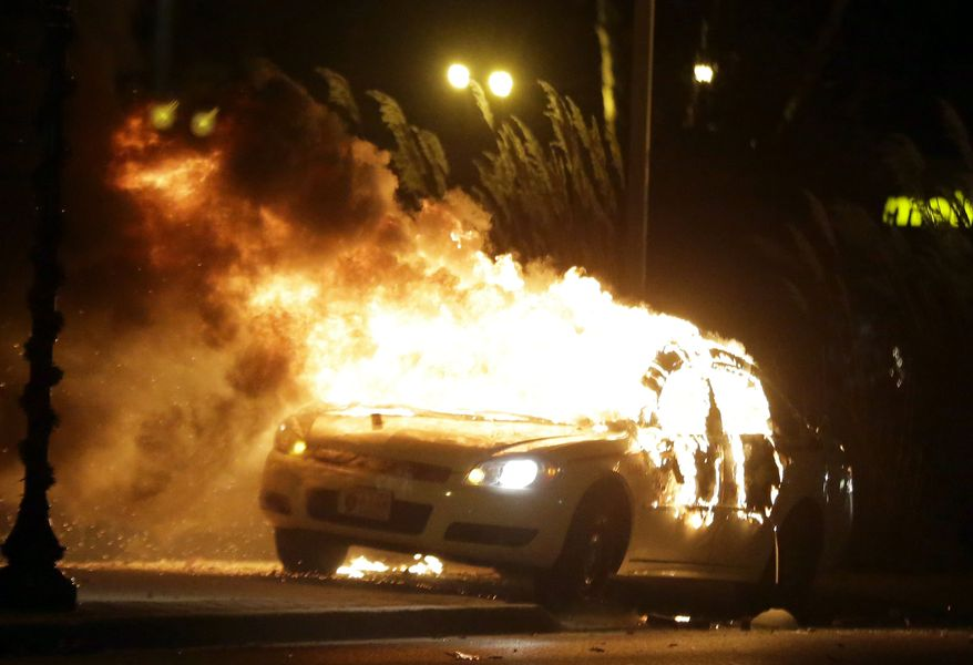A police car is set on fire after a group of protesters vandalize the vehicle after the announcement of the grand jury decision Monday, Nov. 24, 2014, in Ferguson, Mo. A grand jury has decided not to indict Ferguson police officer Darren Wilson in the death of Michael Brown, the unarmed, black 18-year-old whose fatal shooting sparked sometimes violent protests. (AP Photo/Charlie Riedel)