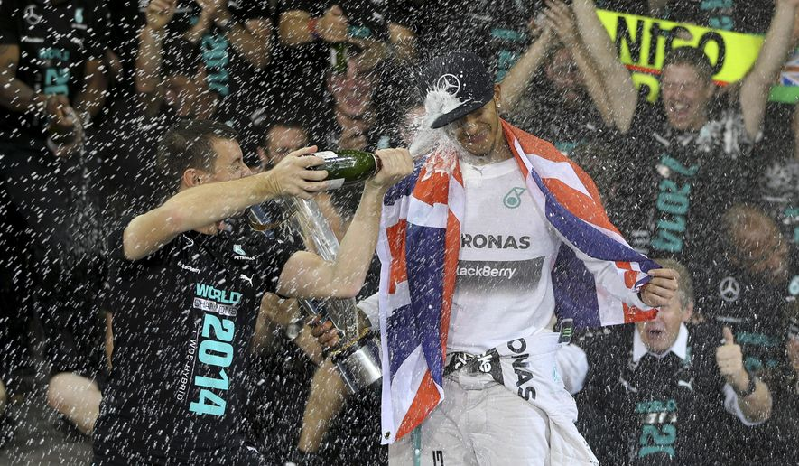 Mercedes driver Lewis Hamilton of Britain is sprayed by a mechanic with champagne in the Mercedes pits after winning the Emirates Formula One Grand Prix to clinch the Formula One world championship at the Yas Marina racetrack in Abu Dhabi, United Arab Emirates, Sunday, Nov. 23, 2014.  (AP Photo/Kamran Jebreili)
