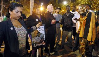 People hold hands in a prayer for peace at the Leimert Park area of Los Angeles, Monday, Nov. 24, 2014. A grand jury has decided not to indict Ferguson police officer Darren Wilson in the fatal shooting of Michael Brown, an unarmed black 18-year-old.. (AP Photo/Nick Ut)