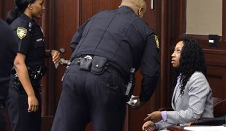 """Marissa Alexander, right, listens to a Sheriff's deputy during a hearing Monday, Nov. 24, 2014, in Jacksonville, Fla. Alexander, accused of firing a gun at her estranged husband and his two sons in what she said was self-defense took a plea deal on Monday, in a case that first got attention because her attorneys used Florida's """"stand your ground"""" law in its defense, arguing that she feared for her life before discharging the weapon. She will receive credit for the 1,030 days she has already serve. She must serve 65 more days and will return to jail Monday.  Had the 34-year-old Alexander, of Jacksonville, been convicted of all counts at her second trial in the case, set to begin Dec. 1, she would have had to serve 60 years because of Florida's minimum-mandatory sentencing rules when a firearm is involved.  (AP Photo/The Florida Times-Union, Bruce Lipsky, Pool)"""