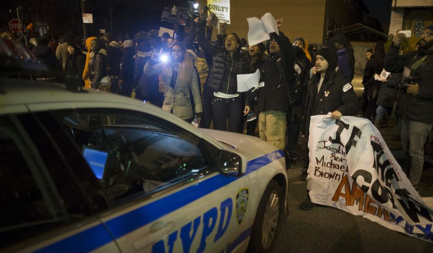 Demonstrators chant outside the 75th Police Precinct in New York. (AP Photo/John Minchillo)