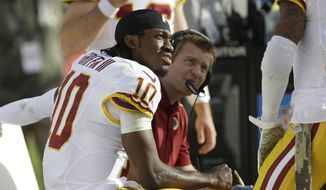 Washington Redskins quarterback Robert Griffin III (10) sits on the sideline during the second quarter of an NFL football game against the San Francisco 49ers in Santa Clara, Calif., Sunday, Nov. 23, 2014. (AP Photo/Ben Margot)