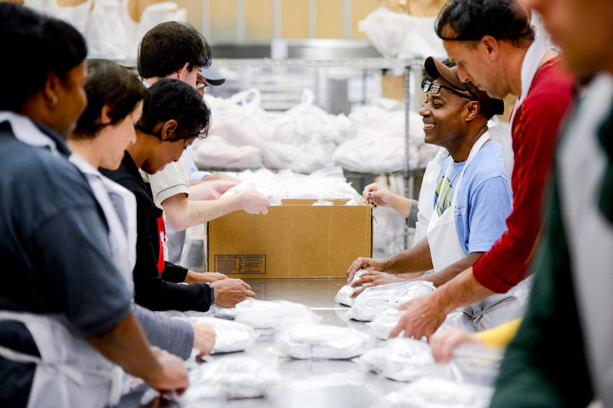 Alex Brown with Food and Friends, a non-profit organization that provides meals and groceries to people living with HIV/AIDS, cancer and other life-challenging illnesses helps volunteers package food before Thanksgiving, Washington, D.C., Monday, November 24, 2014. Food and Friends will deliver almost 900 turkeys and sides on Thanksgiving which will total about 3500 meals. (Andrew Harnik/The Washington Times)