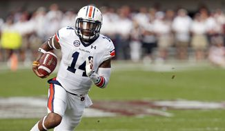 FILE - In this Oct. 11, 2014, file photo, Auburn quarterback Nick Marshall (14) runs upfield for a gain against Mississippi State in the first half of their NCAA college football game in Starkville, Miss. Alabama quarterback Blake Sims is getting his first start in the Iron Bowl during his final game at Bryant-Denny Stadium. Auburn's Nick Marshall has already delivered a huge play in the rivalry game.  (AP Photo/Rogelio V. Solis, File)