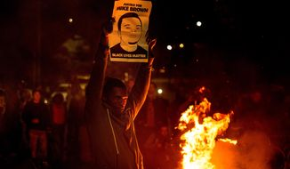 A demonstrator holds a protest sign in Oakland, Calif., on Monday, Nov. 24, 2014,  after the announcement of the grand jury decision not to indict Ferguson police officer Darren Wilson in the fatal shooting of Michael Brown, an unarmed black 18-year-old. (AP Photo/Noah Berger)