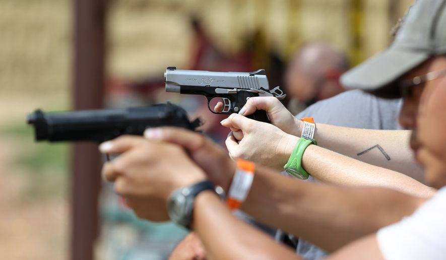 In this July 20, 2014, photo, shooters practice with pistols at the gun range at Dragonman's, a gun dealer east of Colorado Springs, Colo. (AP Photo/Brennan Linsley) ** FILE **