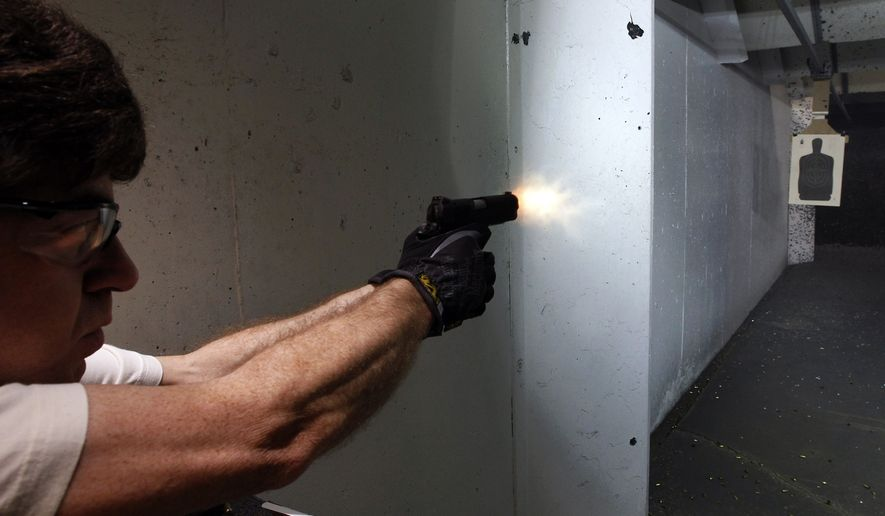 Dimitry Lazar fires his 9mm pistol at targets at the Firing-Line indoor range and gun shop, Thursday, July 26, 2012, in Aurora, Colo. (AP Photo/Alex Brandon) ** FILE **