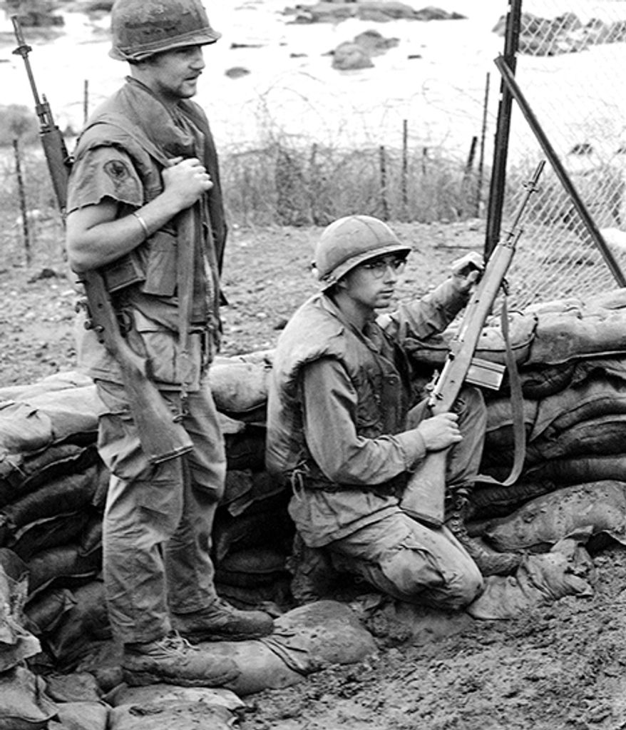 M14 - an American selective fire automatic rifle that fires (.308 Winchester) ammunition. It gradually replaced the M1 Garand in U.S. Army service by 1961 and in U.S. Marine Corps service by 1965. It was the standard issue infantry rifle for U.S. military personnel in the Contiguous United States, Europe, and South Korea from 1959 until it was replaced by the M16 rifle in 1970. The M14 was used for U.S. Army, Coast Guard and Marine Corps basic and advanced individual training from the mid-1960s to the early 1970s. The M14 was the last American 'battle rifle' (weapons that fire full-power rifle ammunition) issued in quantity to U.S. military personnel. The rifle remains in limited service in all branches of the U.S. military as an accurized competition and sniping weapon. It is also used as a ceremonial weapon by honor guards, color guards, drill teams, and ceremonial guards. The M14 serves as the basis for the M21 and M25 sniper rifles.SP4 Michael Ferreira, left, Dallas, Tex., and SP4 David Booker, Geneva, Indiana, keep close watch during their guard duty tour on the Dak To perimeter with their M14 weapons in Vietnam on June 11, 1969. American defenders have beaten off enemy attacks in the area on 24 of the last 31 nights. (AP Photo/Cornu)