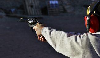 This Dec. 23, 2012 file photo, a man shoots a revolver, at Dragonman's firing range and gun dealer, outside Colorado Springs, Colo. (AP Photo/Brennan Linsley, File)