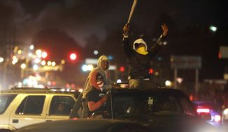 Protesters ride around after the announcement of the grand jury decision Monday, Nov. 24, 2014, in Ferguson, Mo. A grand jury has decided not to indict Ferguson police officer Darren Wilson in the death of Michael Brown, the unarmed, black 18-year-old whose fatal shooting sparked sometimes violent protests. (AP Photo/David Goldman)