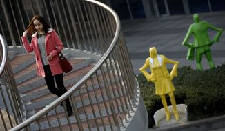 A Chinese woman flips her hair as she walks down an oval staircase near life-size sculptures of shoppers on display outside a shopping mall in Beijing, China Tuesday, Nov. 25, 2014. (AP Photo/Andy Wong)