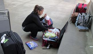 Alfreda Camcaho tries to rearrange her luggage to make room for Christmas presents she's brining back home to Saipan at Honolulu International Airport on Tuesday, Nov. 25, 2014, in Honolulu. (AP Photo/Jennifer Sinco Kelleher)