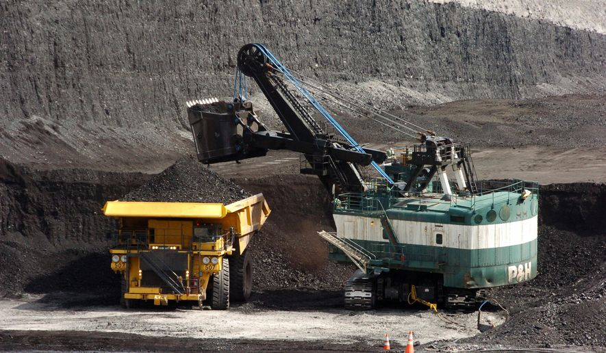 In this April 4, 2013 file photo, a mechanized shovel loads coal onto a haul truck at the Cloud Peak Energy's Spring Creek mine near Decker, Mont. Montana tax authorities argue Tuesday, Nov. 25, 2014, before the state Supreme Court that a Wyoming mining company owes $3.4 million for selling coal to an affiliate at less than market value. At issue is whether coal should be valued for tax purposes at the time the fuel is mined and shipped or when a sale is negotiated. (AP Photo/Matthew Brown, File)