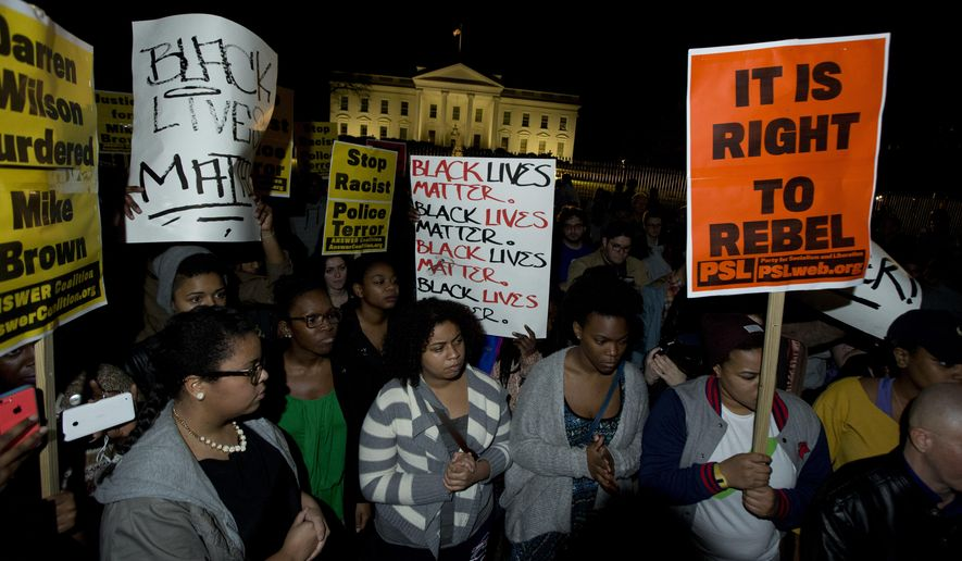 Protestors carry signs and gather in front of the White House in Washington, Tuesday, Nov. 25, 2014, after the Ferguson grand jury decided not to indict police officer Darren Wilson in the shooting death of Michael Brown. (Associated Press)