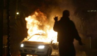 A police car is set on fire after a group of protesters vandalize the vehicle after the announcement of the grand jury decision Monday, Nov. 24, 2014, in Ferguson, Mo. (AP Photo/Charlie Riedel) ** FILE **