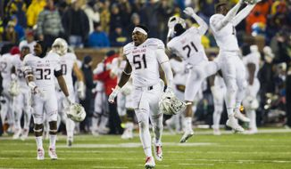 Maryland linebacker Yannik Cudjoe-Virgil (51) celebrates on the field at the end of an NCAA college football game against Michigan in Ann Arbor, Mich., Saturday, Nov. 22, 2014. Maryland won 23-16. (AP Photo/Tony Ding)