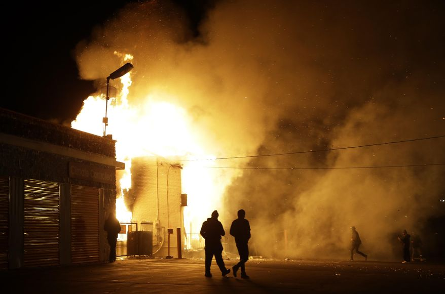 People walk away from a storage facility on fire after the announcement of the grand jury decision Monday, Nov. 24, 2014, in Ferguson, Mo. A grand jury has decided not to indict Ferguson police officer Darren Wilson in the death of Michael Brown, the unarmed, black 18-year-old whose fatal shooting sparked sometimes violent protests. (AP Photo/Jeff Roberson)